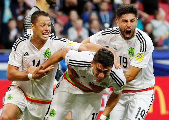 Mexico's Hector Moreno celebrates with Javier Hernandez and Oribe Peralta after scoring the late equaliser against Portugal on Sunday