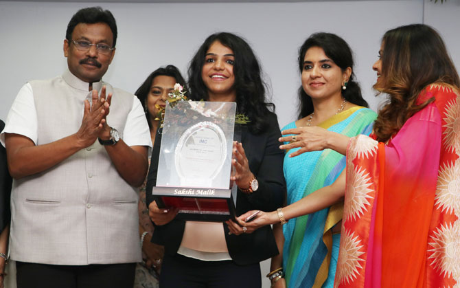 State Minister Sports, Youth Affairs and Education (Maharashtra), Vinod Tawde and BJP member and designer Shaina NC (right) present Saskhi Malik with the Woman of the Year Award at a function hosted by the Ladies' Wing of IMC Chamber of Commerce & Industry, in Mumbai on Wednesday