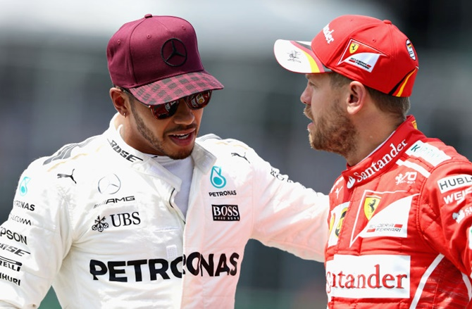 Lewis Hamilton of Great Britain and Mercedes GP talks with Sebastian Vettel of Germany and Ferrari