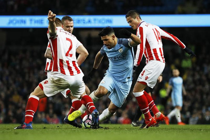 Manchester City's Sergio Aguero is challenged by Stoke City's Ibrahim Affelay and Phil Bardsley