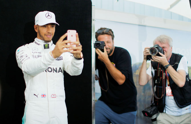 Mercedes driver Lewis Hamilton takes a selfie during the driver portrait session at the first race of the year at the Australian F1 GP in Melbourne, on Thursday, March 23