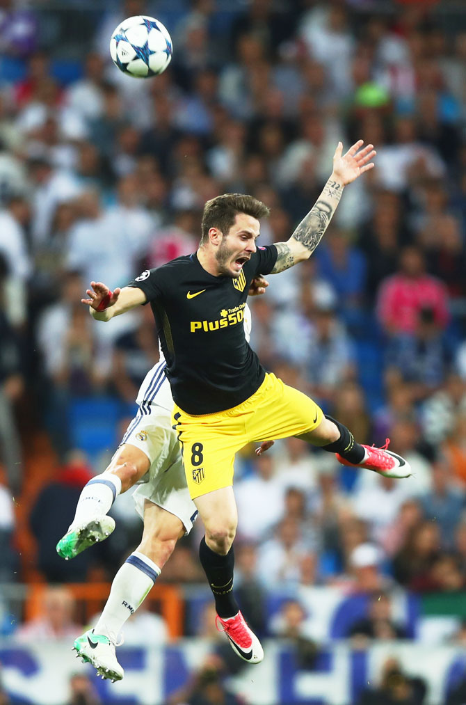tletico Madrid's Saul Niguez is involved in an aerial possession with a Real Madrid player