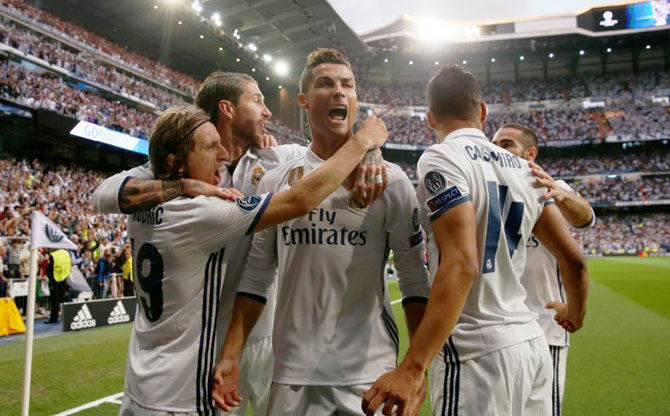 Real Madrid players celebrate after Cristiano Ronaldo scores the opening goal against Atletico Madrid during the Champions League first leg semi-final at the Santiago Bernabeu in Madrid on Tuesday