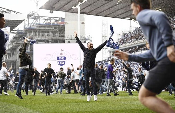 Fans of Tottenham Hotspur invade the pitch after the team's 2-1 win over Manchester United in White Hart Lane's final match on Sunday