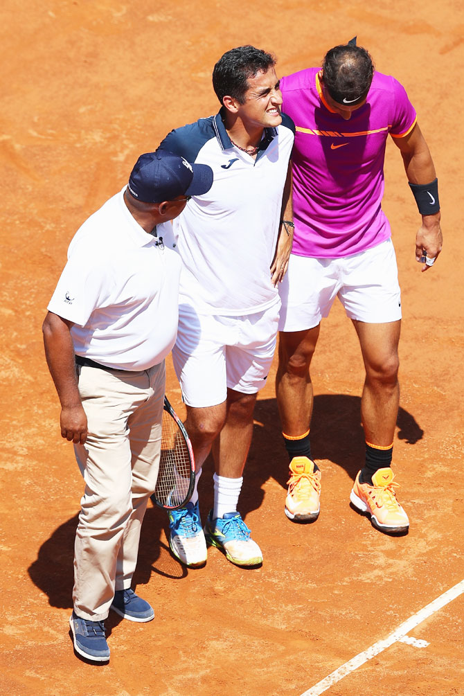 Spain's Nicolas Almagro (centre) is helped off court by Rafael Nadal (right) and umpire Carlos Bernardes (left) after retiring at 0-3 in the opening set on Day Four of The Internazionali BNL d'Italia 2017 at the Foro Italico in Rome, Italy, on Wednesday