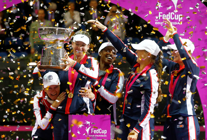 Members of the US team celebrate with the trophy after defeating Belarus in the Fed Cup Final on Sunday