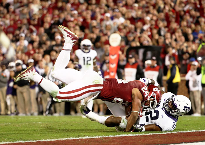 Oklahoma Sooners running back Rodney Anderson runs over TCU Horned Frogs linebacker Travin Howard for a touchdown during their NCAA Football tournament on Sunday
