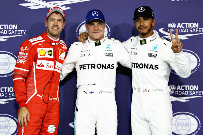 Finland and Mercedes GP's Valtteri Bottas, Great Britain and Mercedes GP's Lewis Hamilton and Germany and Ferrari's Sebastian Vettel pose for a photo in parc ferme during qualifying for the Abu Dhabi Formula One Grand Prix at Yas Marina Circuit in Abu Dhabi, United Arab Emirates, on Saturday