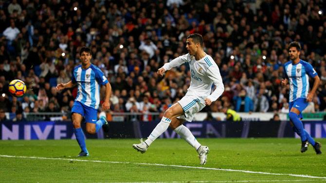 Real Madrid's Cristiano Ronaldo scores their third goal, which is a rebound from a penalty miss during their La Liga match against Malaga at the Santiago Bernabeu in Madrid on Saturday