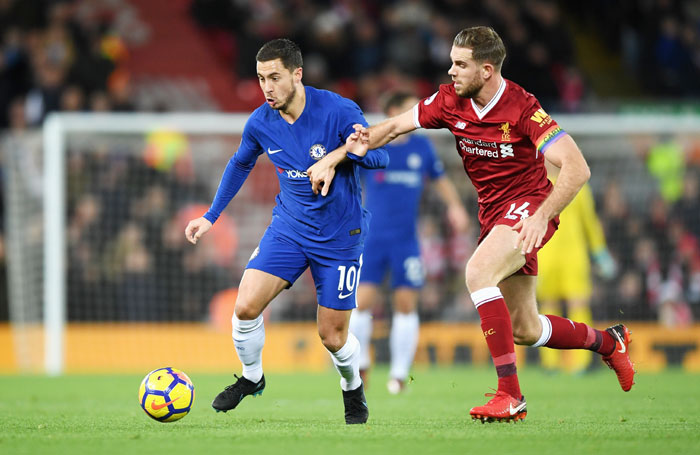 Chelsea's Eden Hazard is challenged by Liverpool's Jordan Henderson as they battle for possession during their English Premier League match at Anfield in Liverpool, England on Saturday