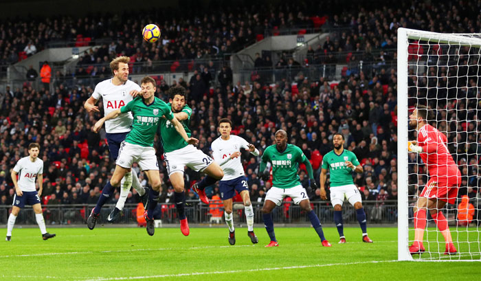 Tottenham's Harry Kane heads at goal as he is involved in an aerial challenge with West Bromwich Albion's Ahmed Hegazi and Jonny Evans