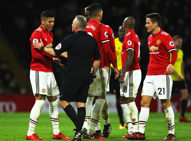 Manchester United's Marcos Rojo (left) in discussion with referee Jonathan Moss during their English Premier League match at Vicarage Road in Watford on Tuesday