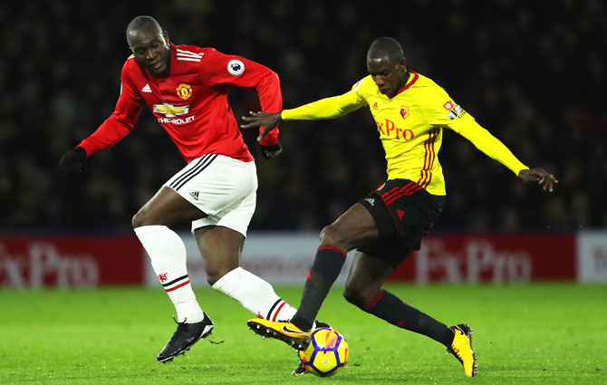 Watford's Abdoulaye Doucoure holds off Manchester United's Romelu Lukaku as they battle for the ball during their English Premier League match at Vicarage Road in Watford on Tuesday
