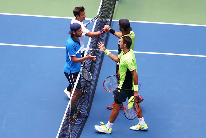 Jean-Julien Rojer and Horia Tecau are congratulated by Feliciano Lopez and Marc Lopez