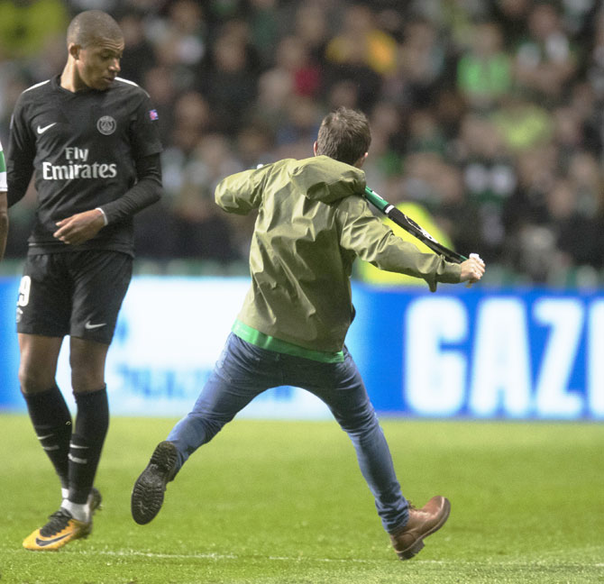 A Celtic fan runs on to the pitch and aims a kick at Paris Saint Germain's Kylian Mbappe during the UEFA Champions League match at Celtic Park Stadium in Glasgow, on Tuesday