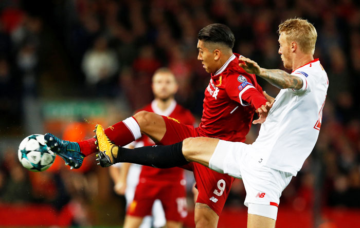 Liverpool's Roberto Firmino and Sevilla's Simon Kjaer vie for possession