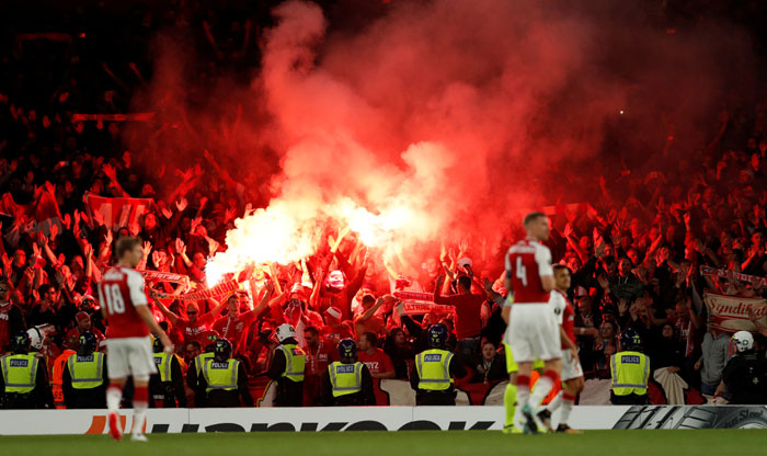 FC Koln fans celebrate their first goal by letting off flares during the Europa League match against Arsenal at Emirates Stadium in London on Thursday