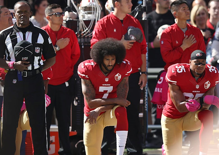 Eric Reid, right, and Colin Kaepernick, centre, of the San Francisco 49ers kneel in protest of racism during the national anthem prior to their NFL game on September 27 last year