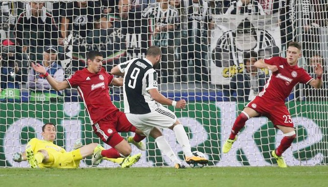 Gonzalo Higuain scores Juventus's first goal against Olympiakos.