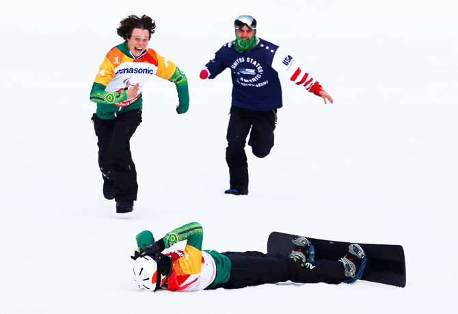 Australia's Simon Patmore lies in the snow after winning the event as fellow competitor Ben Tudhope rushes to congratulate him during the men's snowboard cross SB-UL big final at Jeongseon Alpine Centre in Jeongseon, South Korea at the Pyeongchang 2018 Winter Paralympics on March 12
