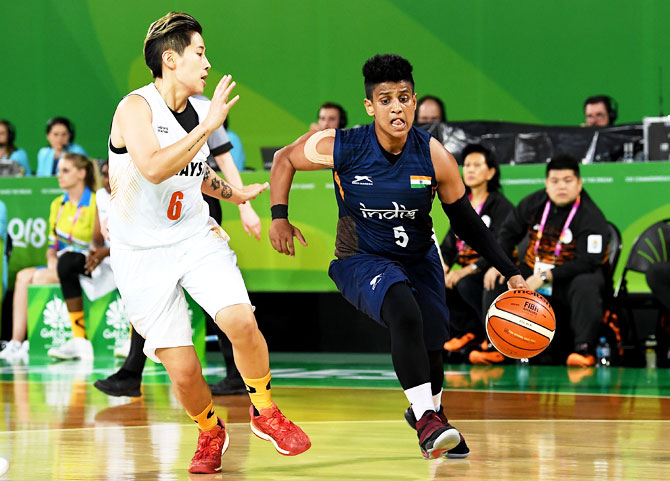 India's Barkha Sonkar breaks away from the defence of Malaysia's Yin Wei Saw during the preliminary round match basketball match against Malaysia at Cairns Convention Centre