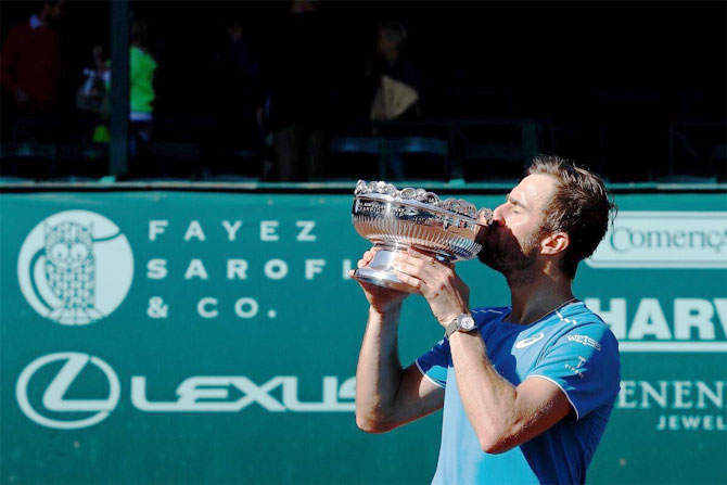 USA's Steve Johnson celebrates with the trophy after winning the Houston Clay Court Championships on Sunday