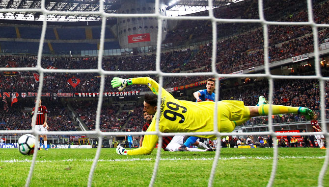 AC Milan's Gianluigi Donnarumma saves a shot from Napoli's Arkadiusz Milik