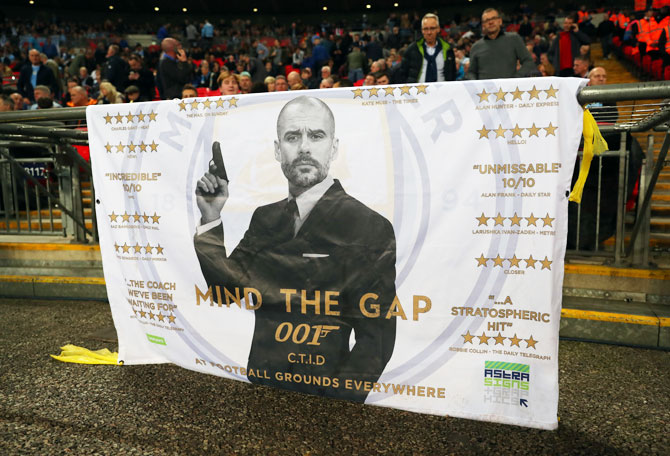 A banner bearing a picture of Manchester City manager Pep Guardiola dressed as James Bond during the Premier League match between Tottenham Hotspur and Manchester City at Wembley Stadium in London on Saturday