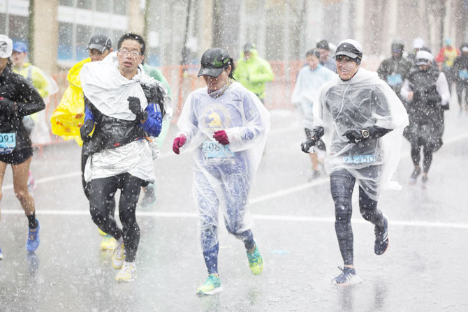 Runners approach the 24 mile marker of the 2018 Boston Marathon in heavy rain