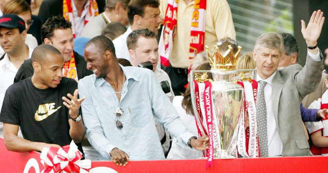 Arsenal's Thierry Henry, Patrick Viera and manager Arsene Wenger celebrate their EPL title-win during a victory parade in north London on May 16, 2004