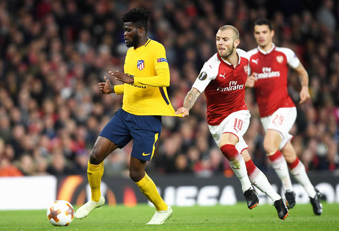 Atletico Madrid's Thomas Partey is pulled back by Arsenal's Jack Wilshere