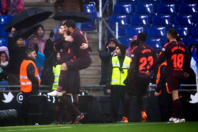 FC Barcelona's Gerard Pique celebrates with teammates after scoring his team's first goal during their La Liga match against Espanyol at RCDE Stadium in Barcelona on Sunday