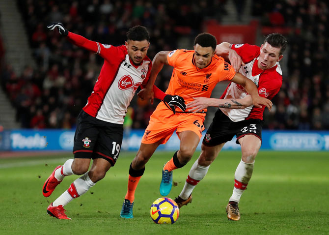 Liverpool's Trent Alexander-Arnold and Southampton's Sofiane Boufal and Pierre-Emile Hojbjerg vie for possession