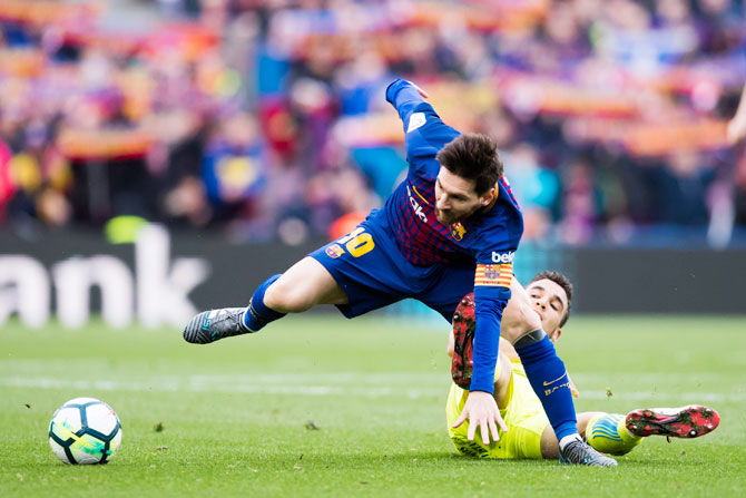Getafe CF'S Mauro Arambarri tackles FC Barcelona's Lionel Messi during their La Liga match at Camp Nou in Barcelona on Sunday