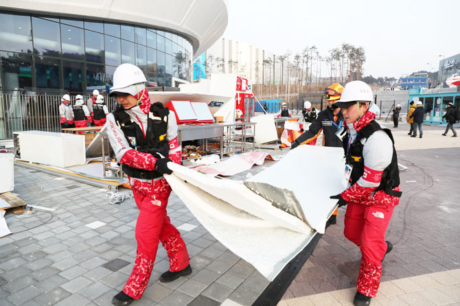 Firefighters remove the debris of a damaged food stall that was blown over by the wind at Gangneung Olympic Park in Gangneung, South Korea on Wednesday