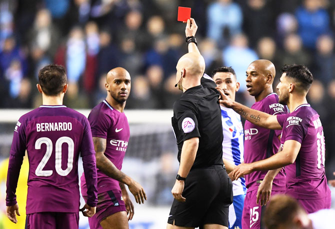 Fabian Delph of Manchester City is shown a red card by referee Anthony Taylor