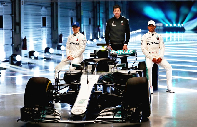 (Left to right) Mercedes GP's Finnish driver Valtteri Bottas, Mercedes GP's Executive Director Toto Wolff and Mercedes GP's British driver Lewis Hamilton pose during the launch of the Mercedes W09 car, at Silverstone Circuit in Northampton, England, on Thursday