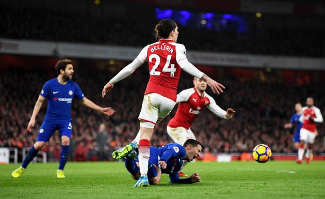 Chelsea's Eden Hazard is fouled by Arsenal's Hector Bellerin leading to Chelsea being awarded a penalty by match referee Anthony Taylor