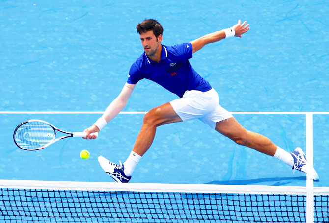 Serbia's Novak Djokovic stretches to play a forehand return during his match against Austria's Dominic Thiem at the Kooyong Classic at Kooyong Lawn Tennis Club in Melbourne on Wednesday