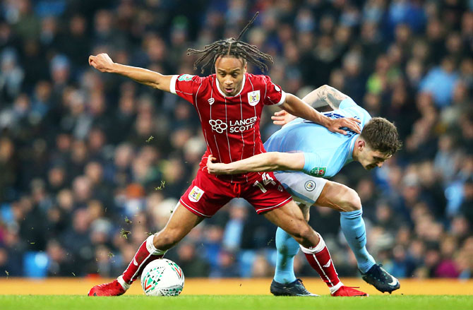 Bristol City' Bobby Reid holds off a challenge by Manchester City's John Stones