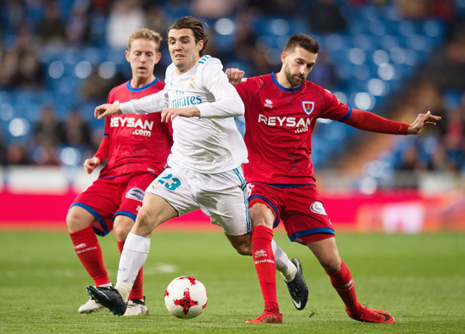 Real Madrid's Mateo Kovacic is tackled by Numancia's Gregorio Sierra (right) during the Copa del Rey, round of 16, second leg match at estadio Santiago Bernabeu in Madrid, on Wednesday