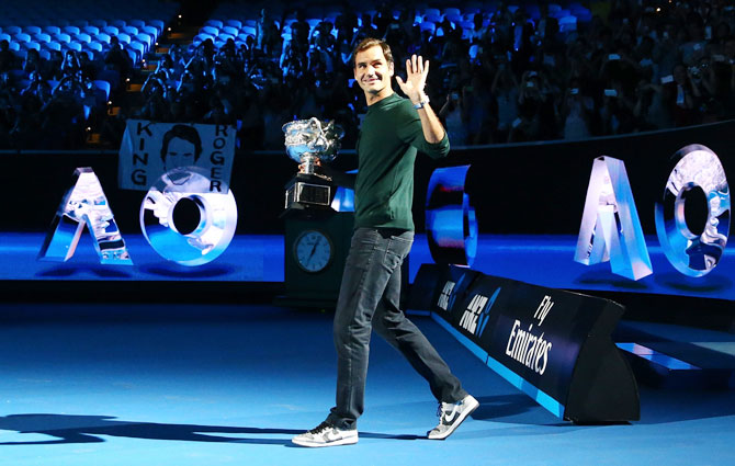 Switzerland's Roger Federer arrives on court with the Norman Brookes trophy at the Australian Open official draw at Melbourne Park on Thursday