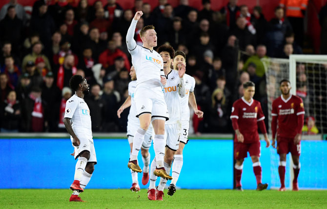 Swansea City's Alfie Mawson celebrates scoring their first goal against Swansea City at Liberty Stadium in Swansea on Monday