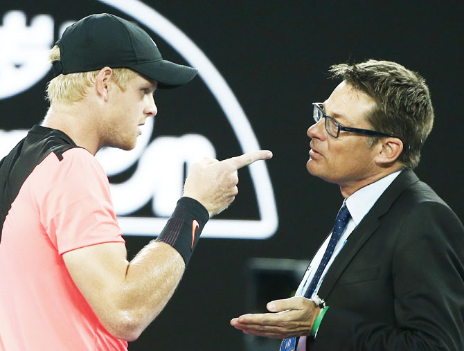 Kyle Edmund speaks with an official after arguing with umpire John Blom