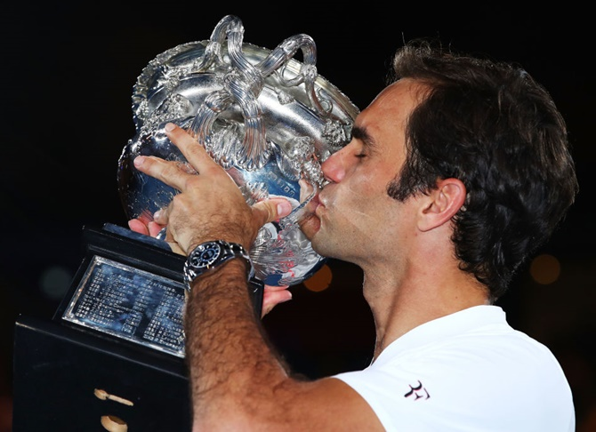 Roger Federer kisses the Norman Brookes Challenge Cup after winning the 2018 Australian Open, his 20th Grand Slam title
