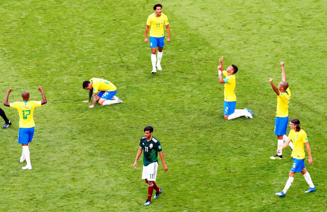 Mexico's Carlos Vela looks dejected as Brazil's Thiago Silva, Marquinhos and teammates celebrate victory after the match