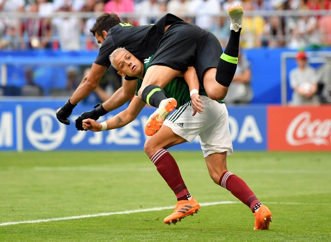 Mexico's Javier Hernandez collides with Brazil goalkeeper Alisson Becker