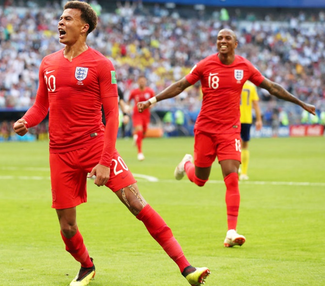 Dele Alli of England celebrates after scoring his team's second goal with teammate Ashley Young