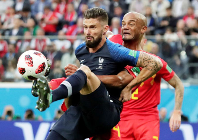France's Olivier Giroud holds off with Belgium's Vincent Kompany as they battle for the ball
