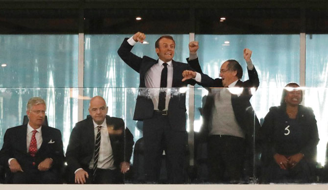 French President Emmanuel Macron (centre) celebrates as King Philippe of Belgium (left) looks on alongside FIFA president Gianni Infantino at the end of the match